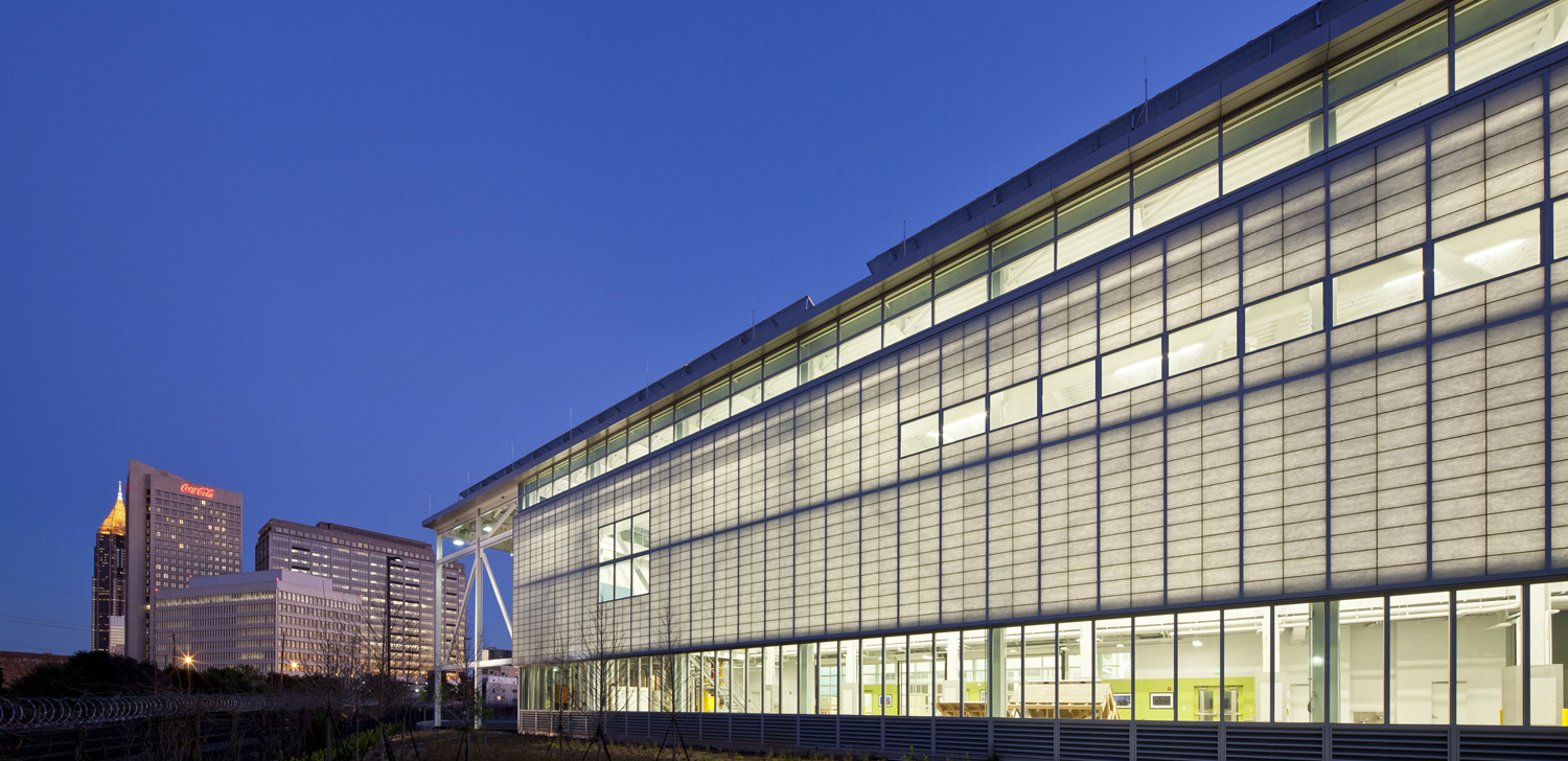 Image of the Carbon Neutral Energy Solutions building at Georgia Tech, at night, lit from within, with the ATL skyline in the background.