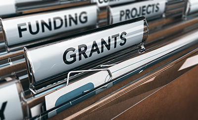 "Image-link to Funding Opportunities. File folders in a drawer with big labels including ""Grants,"" ""Funding,"" and ""Projects."""