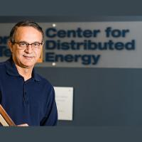 Deepak Divan, Director of the Center for Distributed Energy, stands in front of the CDE sign outside their offices.