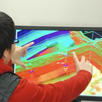 A researcher manipulates a 3-D rendering of subterranean seismic survey data.